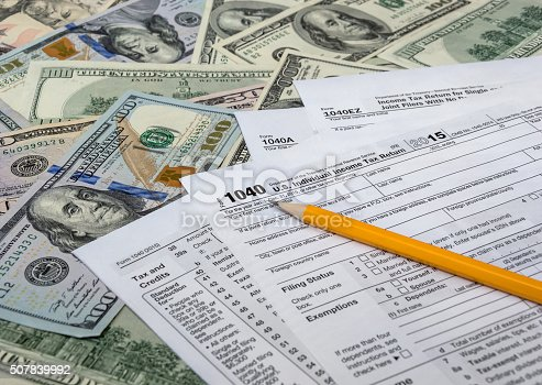 istock Pencil with tax form on US dollarbills background 507839992