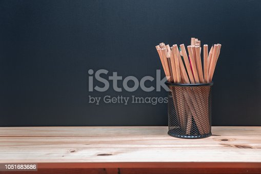 istock Pencils in metal holder pot on wooden table and blackboard background 1051683686