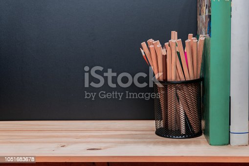 istock Pencils in metal holder pot with books on wooden table and blackboard background 1051683678