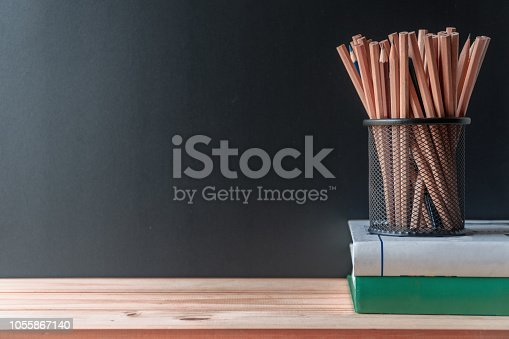istock Pencils in metal holder pot with books on wooden table and blackboard background 1055867140