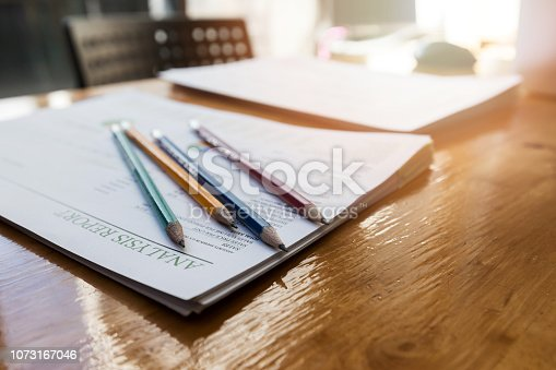 istock Pencils on report paper on wooden desk at the office 1073167046