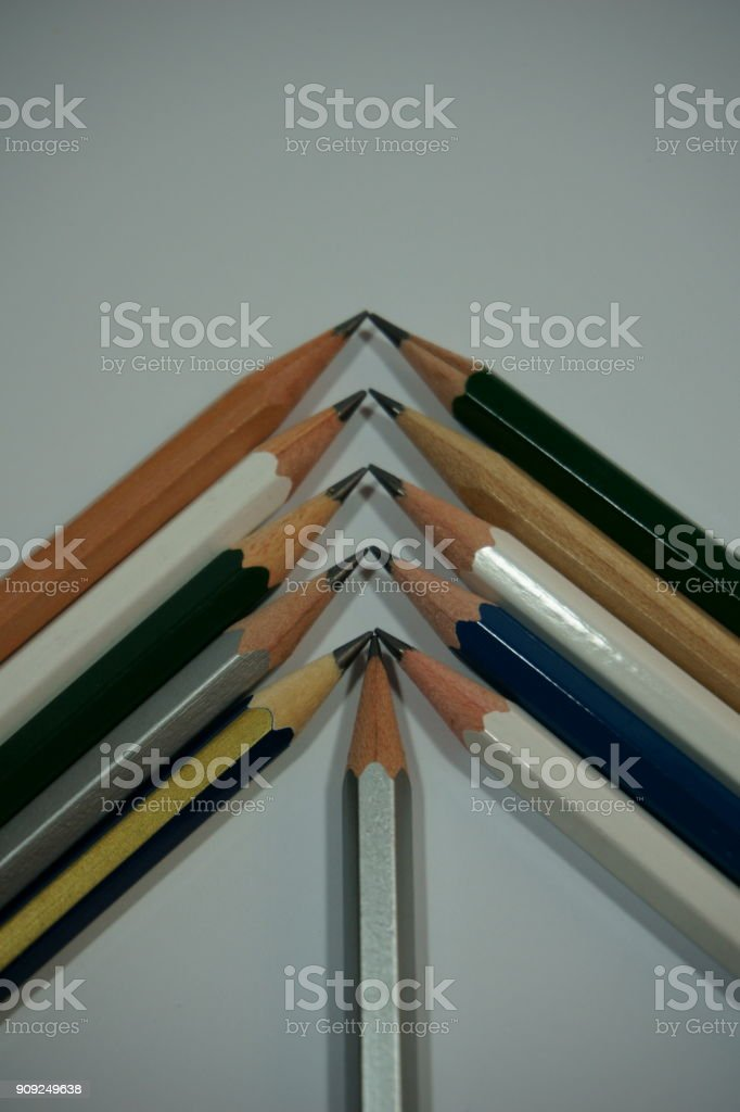 Pencils placed as inverse 'V' pattern on white surface stock photo