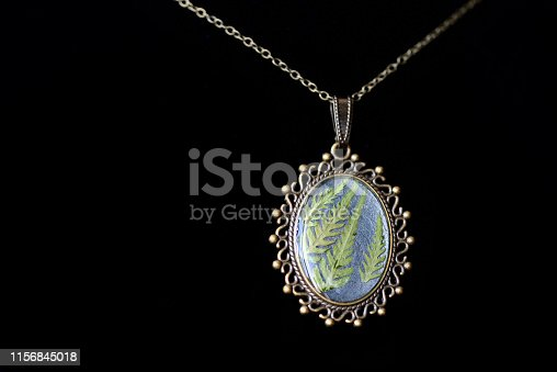 istock Pendant made of epoxy resin and fern leaf on a dark background close up 1156845018