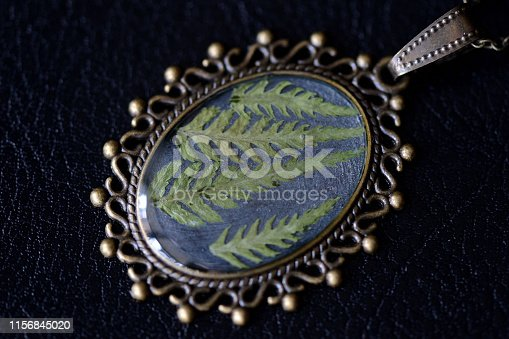 istock Pendant made of epoxy resin and fern leaf on a dark background close up 1156845020