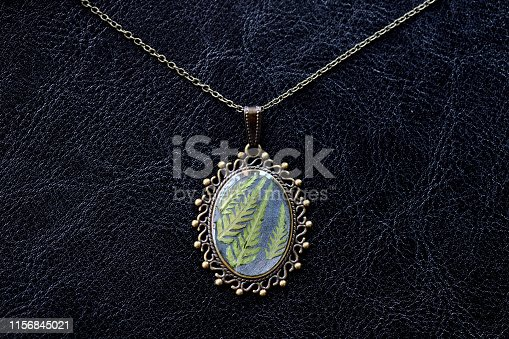istock Pendant made of epoxy resin and fern leaf on a dark background close up 1156845021