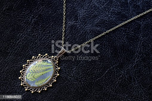 istock Pendant made of epoxy resin and fern leaf on a dark background close up 1156845022
