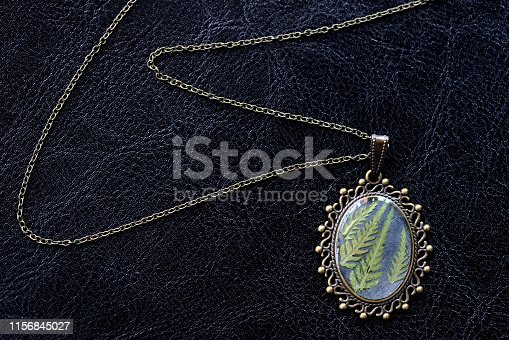 istock Pendant made of epoxy resin and fern leaf on a dark background close up 1156845027
