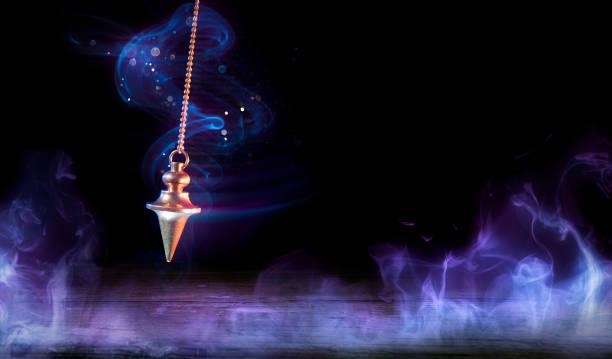 Pendulum Swinging In Magic Background - Occult Concept stock photo