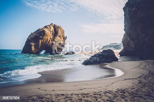 Penedo do Guincho - Santa Cruz Beach, near Lisbon, Portugal: towering rock 98 feet high and 328 feet in circumference with a crack at its base.
