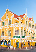 WILLEMSTAD, CURACAO - APRIL 2016: Iconic yellow Penha building on the corner, punda side.