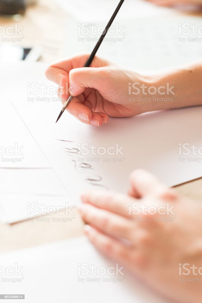 penmanship, hobby, graphic design concept. well groomed hands of young caucasian woman who writing letters of russian alphabeth in harmonious and aesthetic manner with ink and brush stock photo