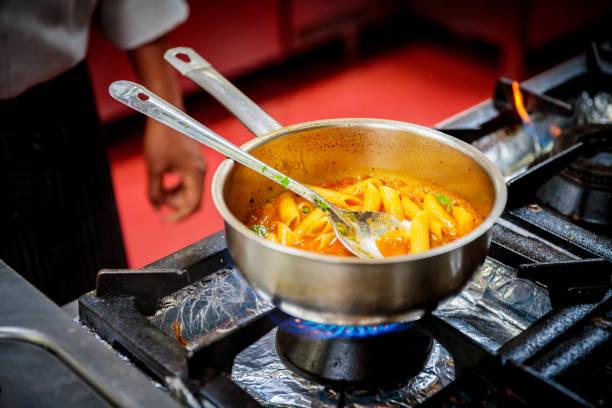 penne pasta kochen im fortschritt - pasta deli stock-fotos und bilder