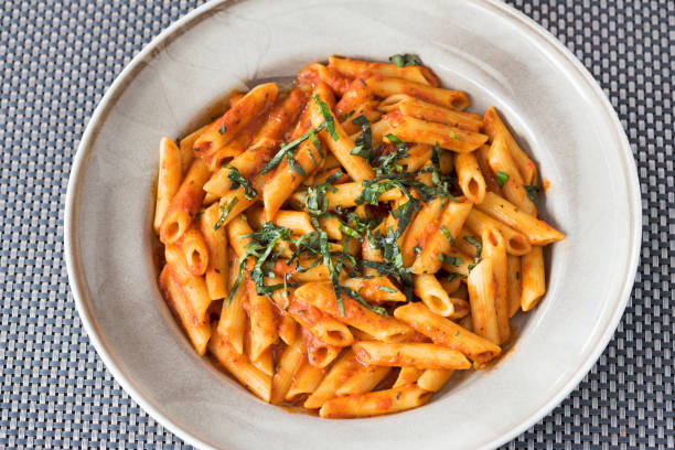 Penne pasta in a spicy sauce made with garlic, tomato and chilli. Penne pasta in a spicy sauce made with garlic, tomato and chilli. rigatoni stock pictures, royalty-free photos & images