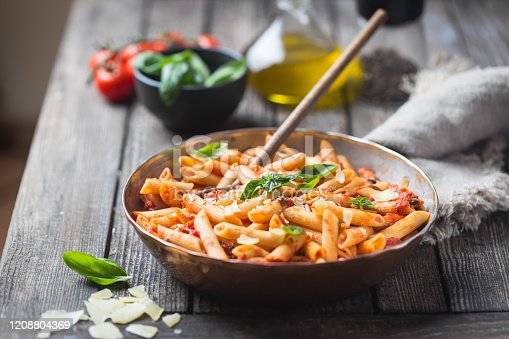 Penne pasta in tomato sauce and cheese decorated with basil on a wooden background