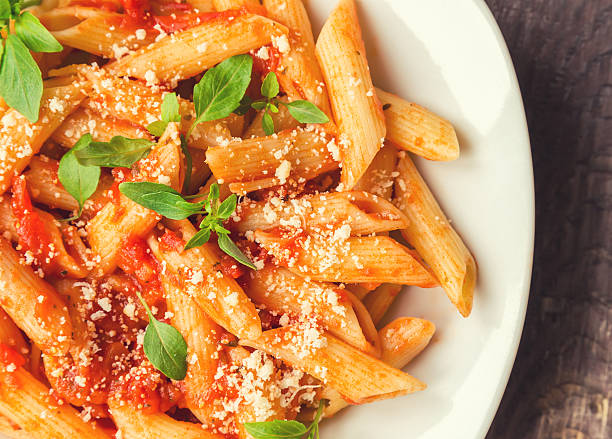 Penne pasta in tomato sauce Penne pasta in tomato sauce with basil and parmesan cheese on rustic wooden background. penne stock pictures, royalty-free photos & images
