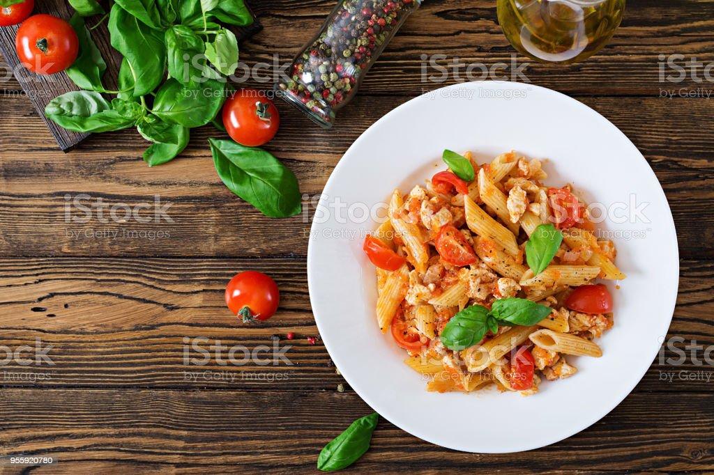 Penne-Nudeln in Tomatensauce mit Huhn, Tomaten, dekoriert mit Basilikum auf einem Holztisch. Italienisches Essen. Pasta Bolognese. Ansicht von oben – Foto