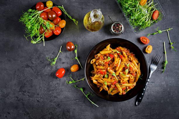 Penne Nudeln in Tomatensauce mit Fleisch, Tomaten mit Erbsen auf einem dunklen Tisch verziert. Top View – Foto