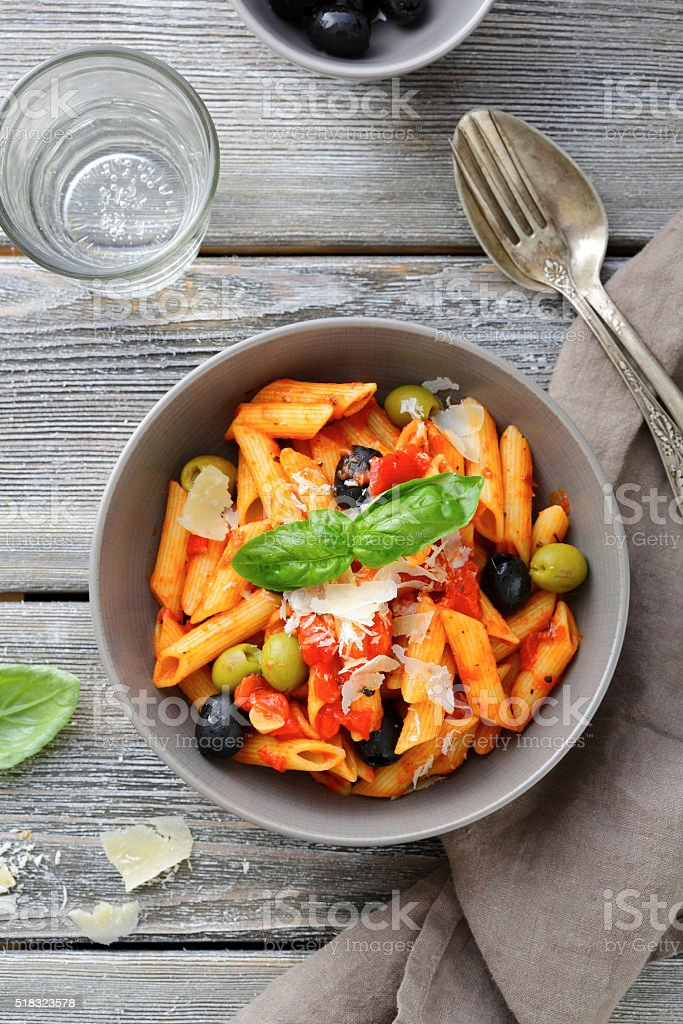 Penne Pasta in tomato sauce with olive and cheese stock photo