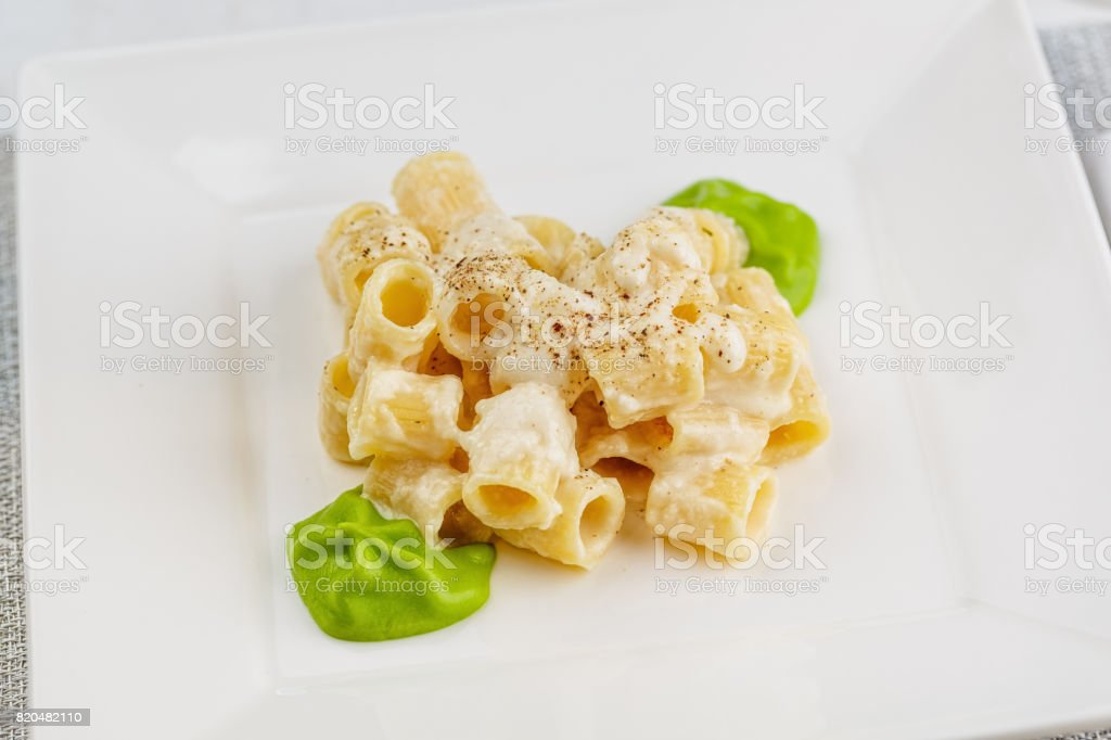 Penne pasta with a creamy sauce with parmesan cheese and spinach sause stock photo