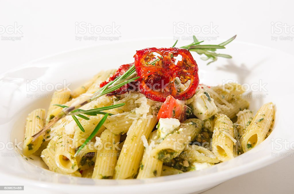 Penne Pasta with cheese feta, spinach, pesto and sun-dried tomat stock photo