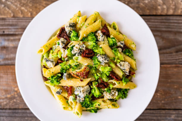 Penne pasta with gorgonzola, sun dried tomatoes and broccoli on wooden table