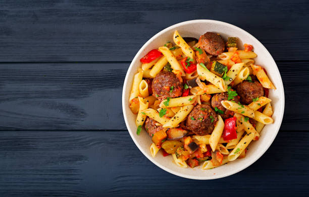 Penne pasta with meatballs in tomato sauce and vegetables in bowl Penne pasta with meatballs in tomato sauce and vegetables in bowl penne stock pictures, royalty-free photos & images