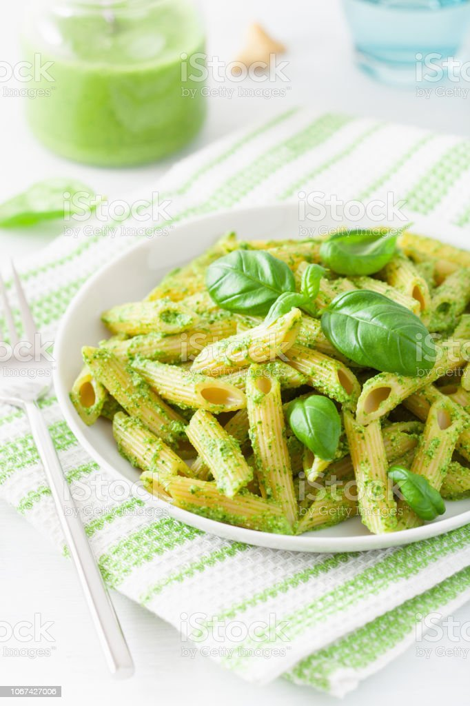 penne pasta with spinach basil pesto sauce stock photo