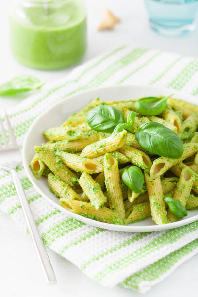 penne pasta with spinach basil pesto sauce penne pasta with spinach basil pesto sauce penne stock pictures, royalty-free photos & images
