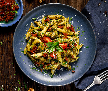 Penne pasta with spinach, sun dried tomatoes and chicken, sprinkled with parmesan cheese and fresh parsley  on a ceramic plate on a wooden rustic table, top view