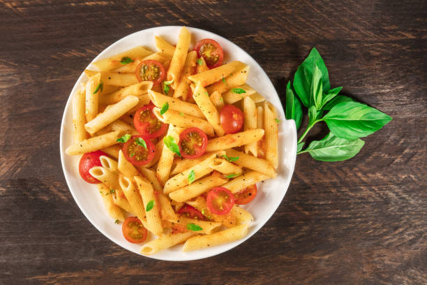 Penne pasta with tomato sauce and fresh basil leaves stock photo