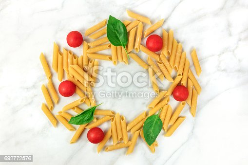 istock Penne rigate, cherry tomatoes, and basil leaves with copyspace 692772576