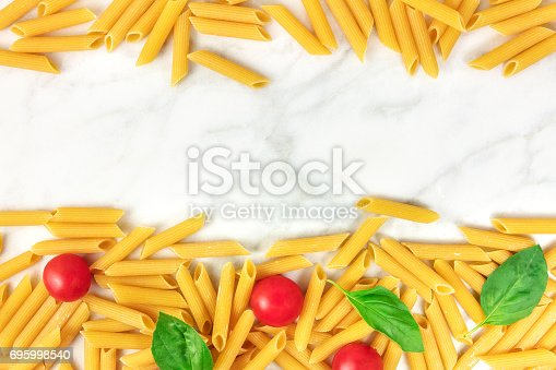 istock Penne rigate, cherry tomatoes, and basil leaves with copyspace 695998540