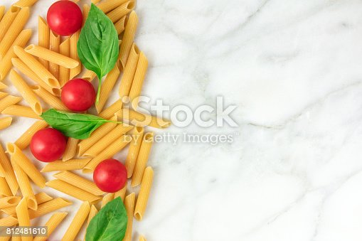 istock Penne rigate, cherry tomatoes, and basil leaves with copyspace 812481610