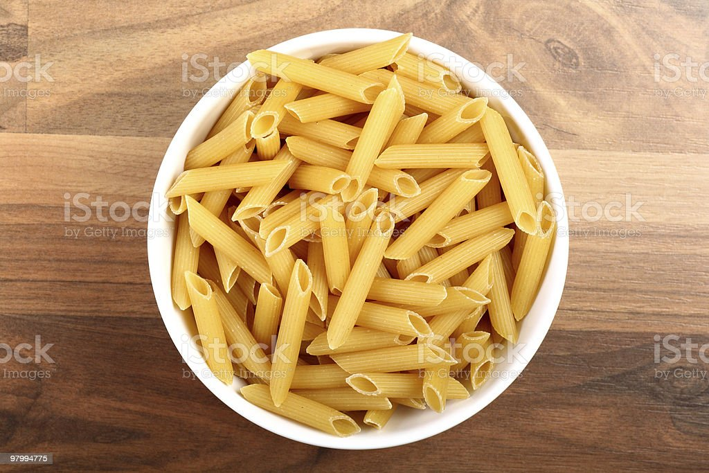 Penne rigate in white ceramic bowl on wooden floor royalty free stockfoto