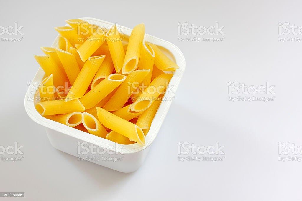 Penne rigate pasta in the plastic box stock photo