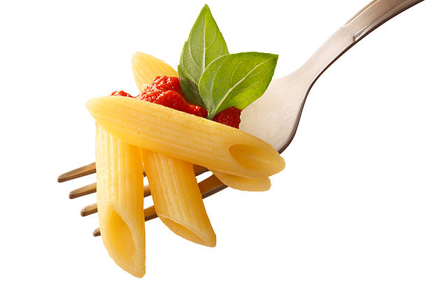 Penne rigate pasta with tomato sauce on a fork Penne rigate pasta with tomato sauce and basil on a fork. Clipping path, infinite depth of field penne stock pictures, royalty-free photos & images