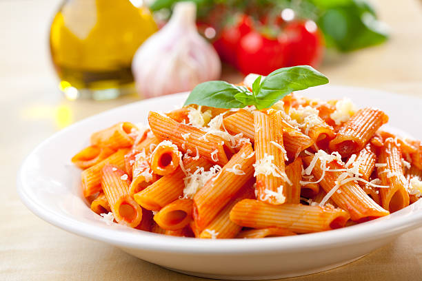 Penne, tomato and basil Plate of penne  with ingredients in the background. penne stock pictures, royalty-free photos & images