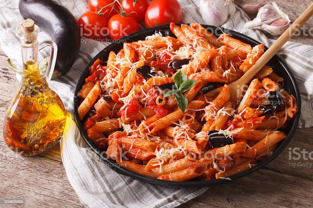 Penne with eggplant and tomatoes closeup and ingredients. horizo stock photo
