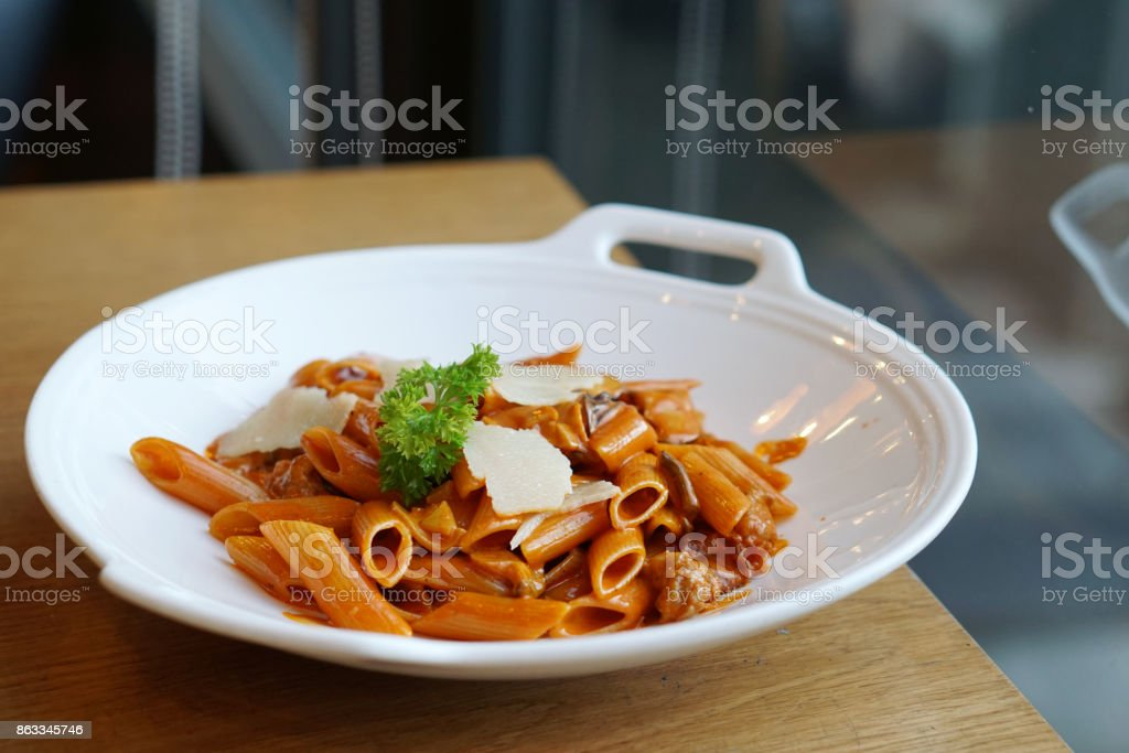 Penne with parma ham, mushroom in vodka and paprika cream sauce. stock photo