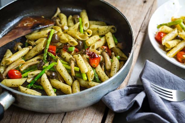 penne mit shimeji pilze und spargel in pesto-sauce in einem topf - spargel vegan stock-fotos und bilder
