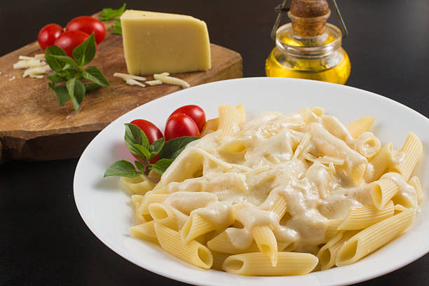 Penne with white sauce Penne with milk cream sauce, cherry tomatoes and basil penne stock pictures, royalty-free photos & images