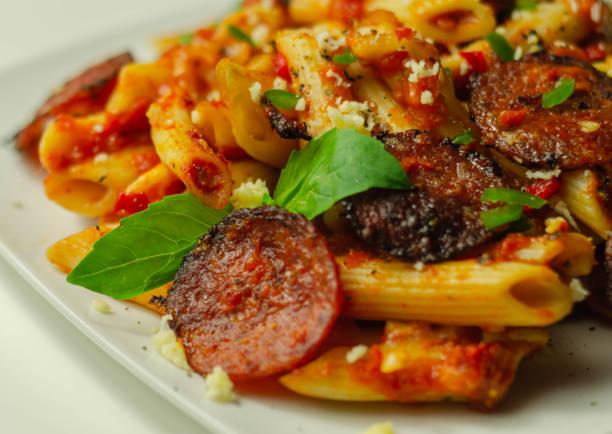 Massa pennette em um molho de tomate picante com pepperoni fatiado, mussarela e queijos cheddar maduros - foto de acervo