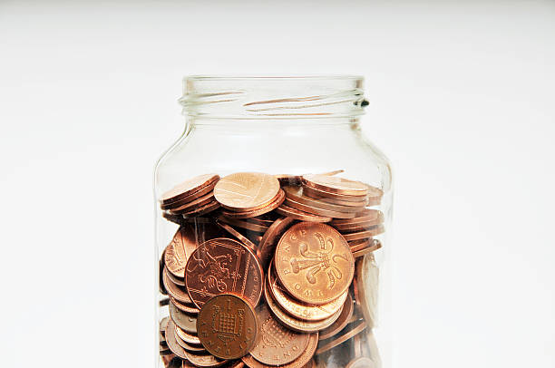 pennies in a savings jar - pound sterling isolated bildbanksfoton och bilder