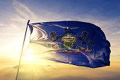 istock Pennsylvania state of United States flag textile cloth fabric waving on the top sunrise mist fog 1063332742