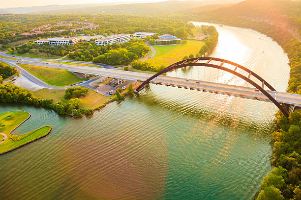 Pennybacker 360 bridge, Colorado River, Austin Texas, aerial panorama Panoramic aerial view from helicopter of 360 bridge on Colorado River near Austin Texas, looking west at sunset. colorado river stock pictures, royalty-free photos & images