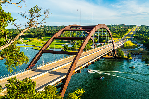501329818 istock photo Pennybacker Bridge Classic View Summer Time with Boat going under bridge 1015130826