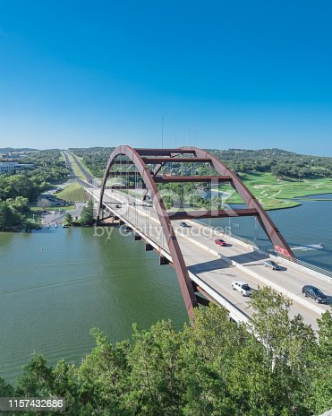 Elevated view of Pennybacker Bridge or 360 Bridge with car traffic at daytime. A landmark in Austin, Texas, USA. Top of Town Lake, Colorado River and Hill Country green landscape