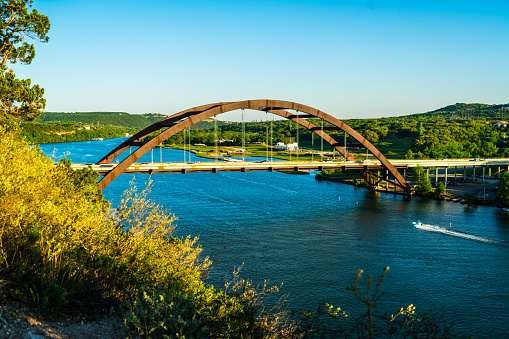 501329818 istock photo Pennybacker brigs or 360 Bridge side angle with boat going under bridge 1132835751
