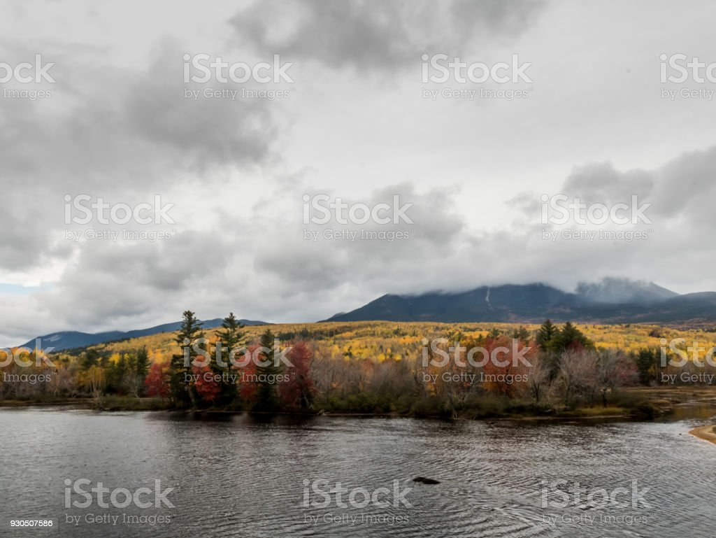 Penobscot River Calmly Flows Below a Cloudy Mount Katahdin stock photo