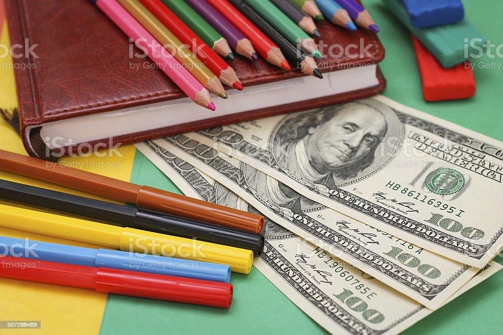 Pens, colored pencils, plasticine, book, hundred dollar bills Pens, colored pencils, plasticine, book, hundred dollar bills Book Stock Photo
